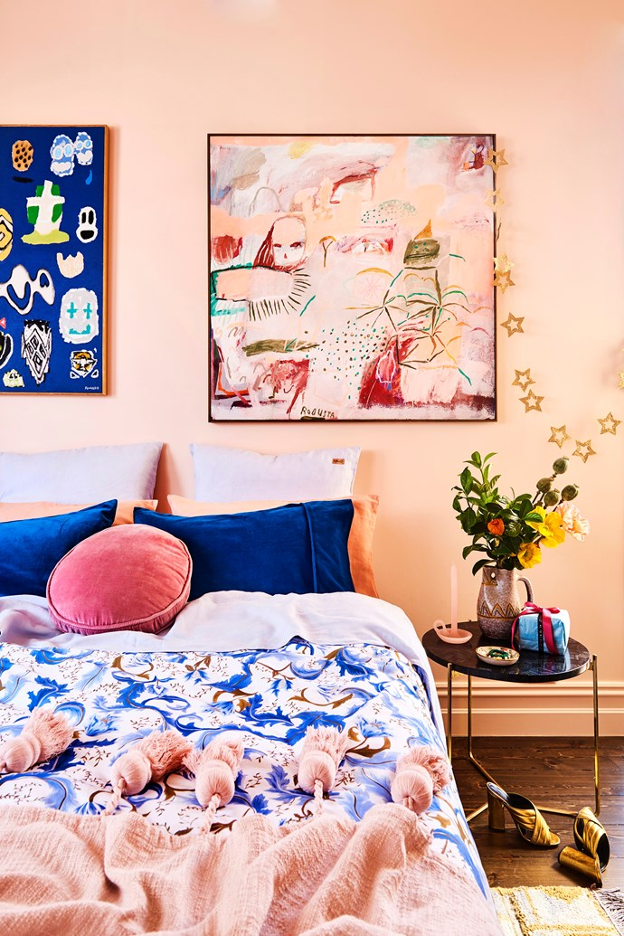 """Like the rest of their home, Bobby and Alex's bedroom is awash with colour! The walls are painted Haymes """"Peach Cascade"""" and hold acrylic artworks by Fred Fowler and Mignon Steele. The Spring In Italy quilt cover, Peach Blush tassel throw, pillowcases and cushions are all Kip&Co – naturally!"""