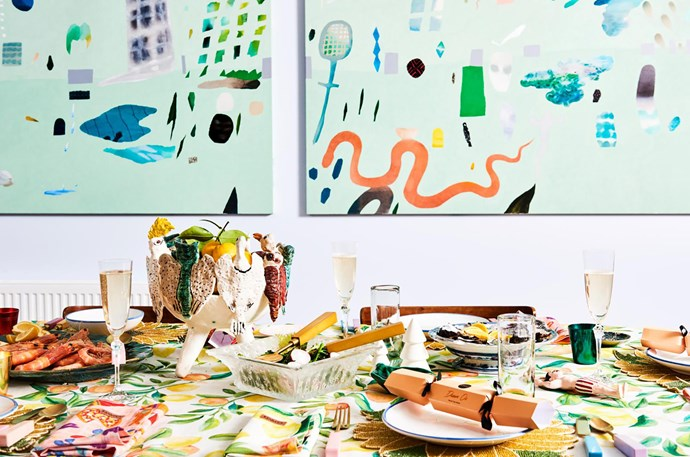 """The key is colour, abundance and maximalism,"""" Alex says of her casual Christmas table, which includes a quirky fruit bowl by Kaye Clancy, Zara Home champagne flutes and serving dishes passed down by family. Three commissioned artworks by Fred Fowler fill the wall behind."""