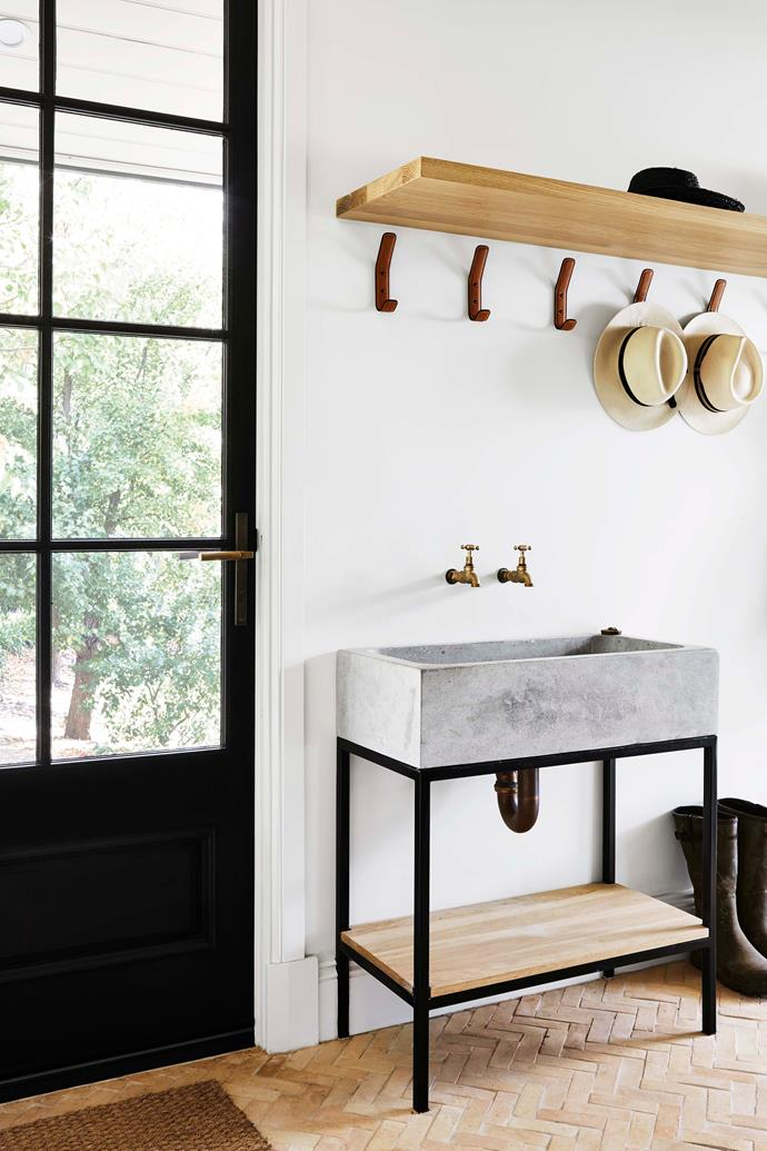 "In the mud room, a concrete sink and herringbone clay tiles are standout features. The leather hooks are from [Made Measure](https://www.mademeasure.com/|target=""_blank"")."