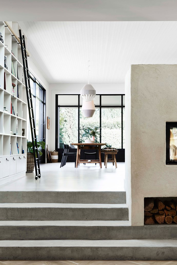 "A double-sided, heavy brick fireplace warms the kitchen, living and dining spaces. Durable materials such as limestone, terracotta, timber, leather and wool were used to harmonise with the 19th-century details that were left intact. Custom ladder and library joinery. 'Dreamweaver' pendant lights from [Pop & Scott](https://www.popandscott.com/|target=""_blank""