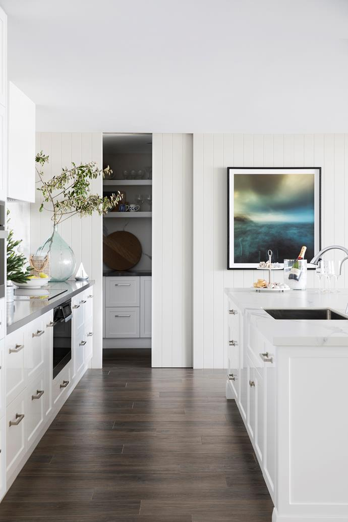 Lining boards on the walls in the kitchen add to the Hamptons vibe, while the sliding-door pantry offers discreet functionality.