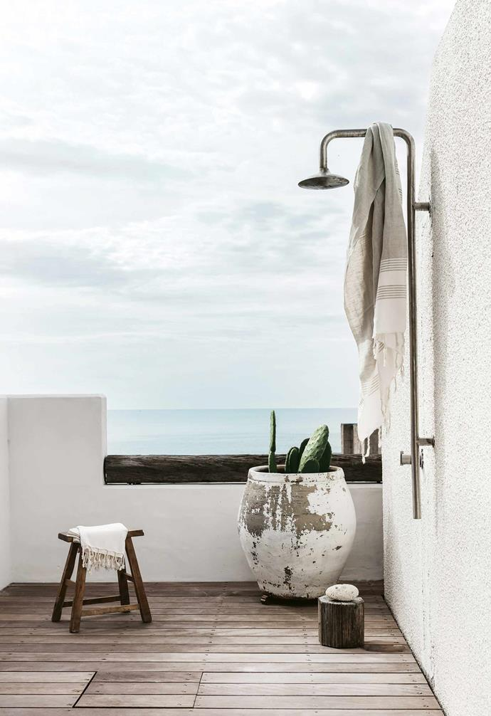"[This Mediterranean-style coastal home](https://www.homestolove.com.au/mediterranean-style-all-white-home-16945|target=""_blank"") takes advantage of its stunning location, with the outdoor shower making the most of stellar views. The weathered deck provides a warm contrast to the white walls surrounding."