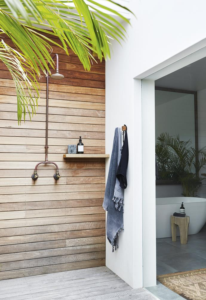 "This simple outdoor shower set-up in this [relaxed all-white Byron Bay home](https://www.homestolove.com.au/relaxed-all-white-byron-bay-home-with-upcycled-details-19266|target=""_blank"") includes a small built-in shelf and towel hooks that's perfect for soaps, shampoos and whatever else you might need, saving the ground from clutter."