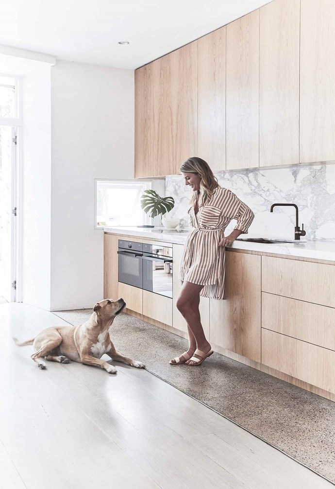 "**Kitchen** Louisa with her dog Sim. The polished concrete floor was part of the original house and fits in with the updates, and the original spotted gum flooring was sanded, limewashed and revived by Mint Floor Sanding & Finishing. Ovens, [V-Zug](https://www.vzug.com/au/en/|target=""_blank""