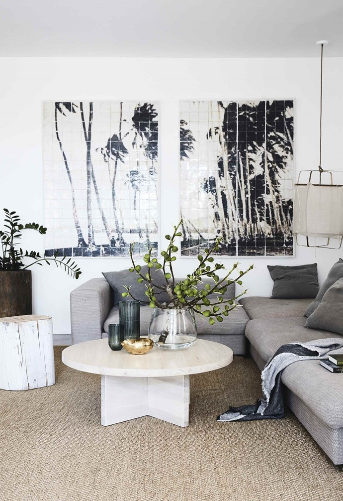 "**Living area** ""The sisal rug was custom made and makes the area seem bigger. It adds to the relaxed feel but still feels elegant,"" says Louisa. The palm tree art is by Byron Bay artist Jai Vasicek. ""The cool tiles work nicely with the linen sofa from Camerich,"" she adds. Ay Illuminate 'z1 black' pendant light, [Spence & Lyda](https://www.spenceandlyda.com.au/