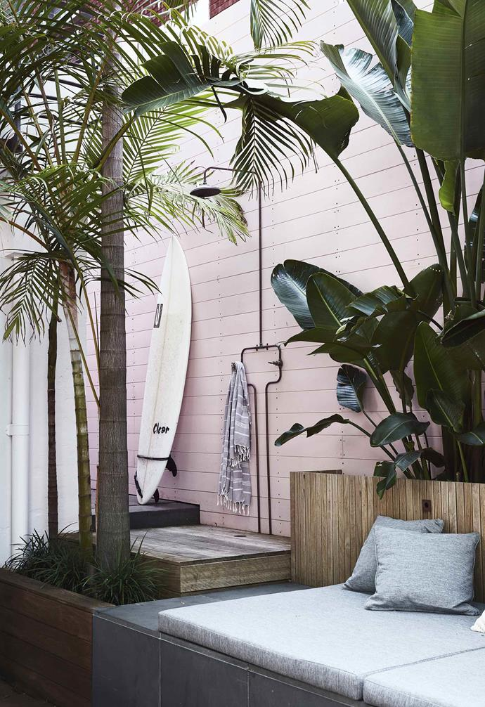 "The pink timber was a shock to the homeowners as they [renovated their Bondi duplex](https://www.homestolove.com.au/duplex-home-renovation-19533|target=""_blank"") but they ended up falling in love with the way the plants popped against it. The simple outdoor shower is tucked amongst trees."