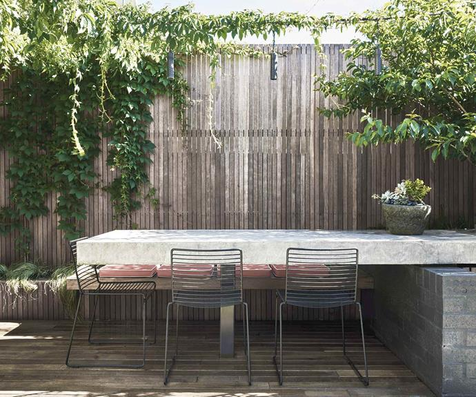"""The hand-trowelled concrete table and barbecue bench, finished with a light grind and then sealed, hold raw appeal. A built-in bench seat in yellow stringybark matches the deck and has been stained to relate to the internal floorboards. Black 'Hee' dining chairs by [Hay](http://hayshop.com.au/ target=""""_blank"""" rel=""""nofollow"""") have a barely there look, perfect for the small space."""