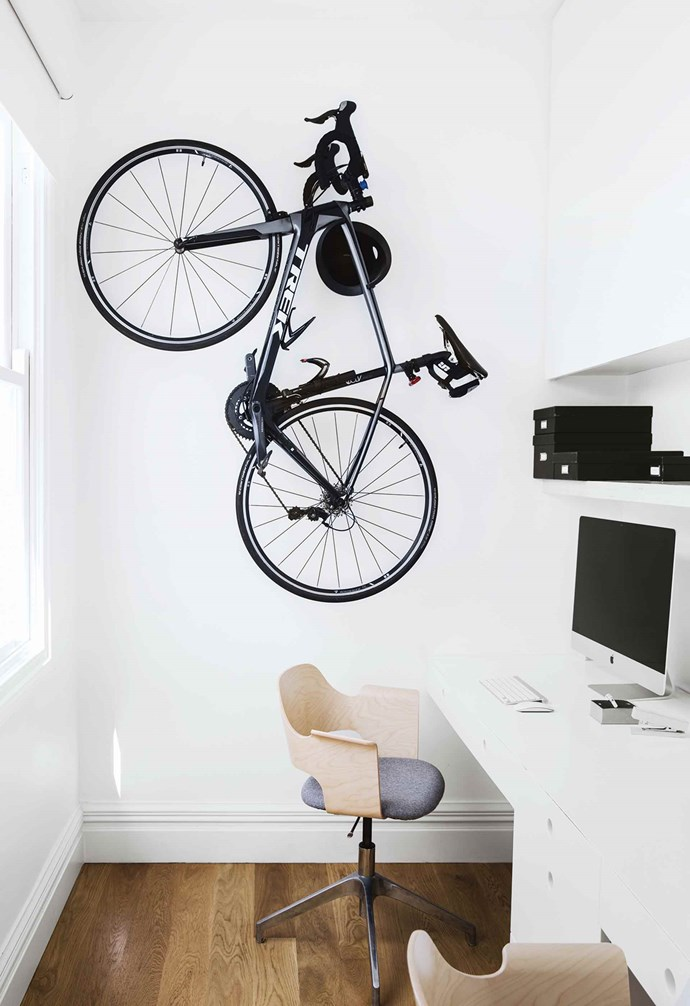 "**Multifunctional** Despite the narrow width of this home office room, the residents of this [minimalist light-filled terrace](https://www.homestolove.com.au/minimalist-inspiration-from-a-light-filled-terrace-18366|target=""_Blank"") added a wall hook for bike storage. ""This could have been another bedroom, but we wanted a workspace for both of us,"" say the homeowners. *Styling: Natalie Walton 
