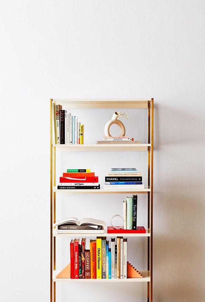 "Zane wide bookshelf in White, $699, West Elm. Oyoy brass bookend, $49, Designstuff. Doiy ""Scala"" bookends, $59.95 for set of 2, Until."