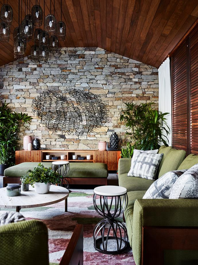 Architect Chris Beckingham used local stone in the stacked stone wall in the living area. Minotti 'Alison Iroko' outdoor sofa and ottoman from De De Ce, travertine coffee table from Spence & Lyda and 'Amalfi' hourglass side tables from Janus et Cie on a Perennials 'Painter's Palette' rug. Artwork by Hannah Quinlivan.