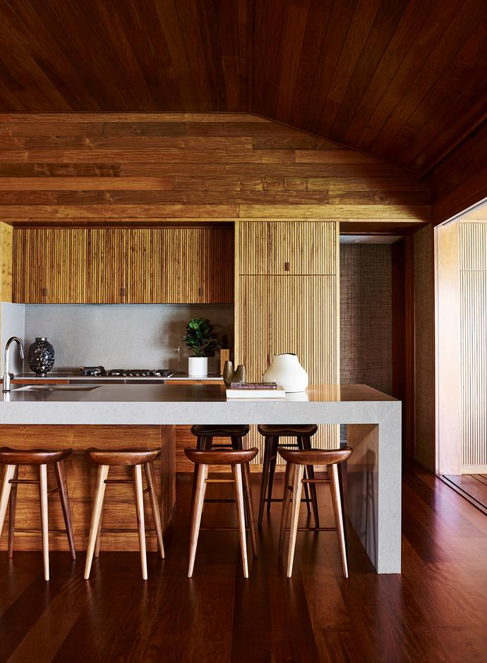 Timber slatted cupboards in the minimalist kitchen. 'Luisa' Portuguese earthenware bowl from Restoration Hardware.
