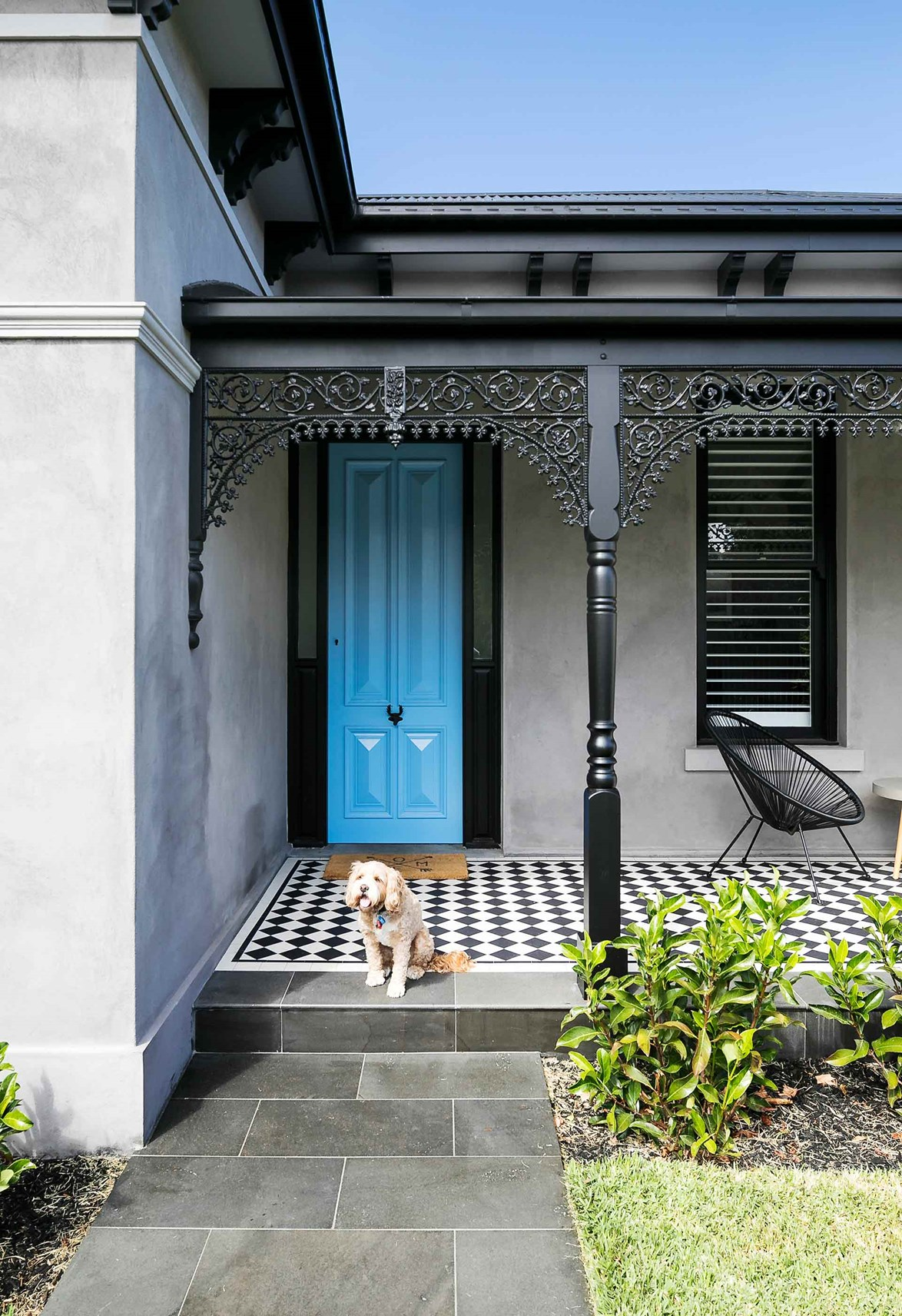 """A vibrant blue front door and patterned monochrome floor tiles add a contemporary touch to the facade of this [restored Victorian home](https://www.homestolove.com.au/century-old-home-renovation-elstenwick-19556