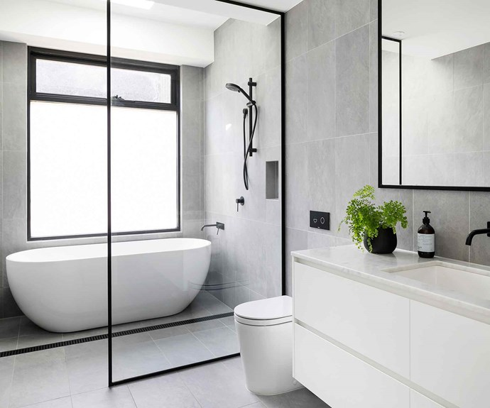 """""""What saved us during the unforced restorations was our [contingency budget](https://www.homestolove.com.au/how-to-manage-your-home-renovation-budget-19107 target=""""_blank""""), so put away more than you think you may need!. Particularly if you're renovating an older period home. I would also suggest that if you have your heart set on a certain feature that is on the more expensive side, like engineered boards, stone bench tops etc, budget for it and be willing to compromise on something else,"""" she continues.<br><br>**Bathroom** The monochrome palette continues in the bathroom with a black-framed glass shower screen complementing the black tapware and trim on the mirror. Large format grey tiles contrast with a white [freestanding bathtub](https://www.homestolove.com.au/freestanding-baths-4520 target=""""_blank"""") and vanity."""