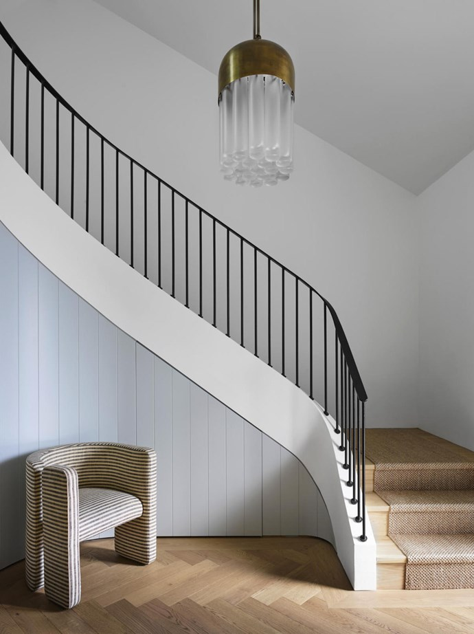 Above the sculptural, redesigned staircase hangs an Apparatus 'Tassel' pendant in aged brass, while a Kelly Wearstler 'Fairfax' chair in ivory and charcoal stripe complements the linear looks of the hallway.