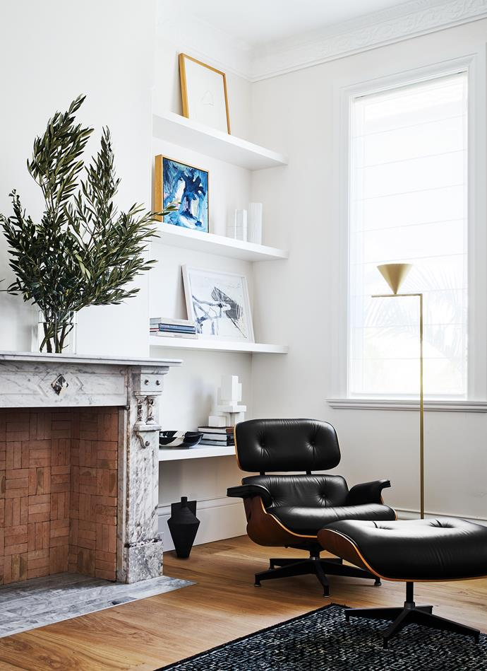 The Eames lounge chair and ottoman denote something of the relaxed feel of this TV room. The original marble fireplace has a contrasting infill of terracotta brick tiles to offset its more mannered quality. On shelves, from top, vintage porcelain vases, Peter Dwyer ceramic bowl and Dan Schneiger sculpture from Becker Minty. Cappellini 'Jana' vase from Cult.