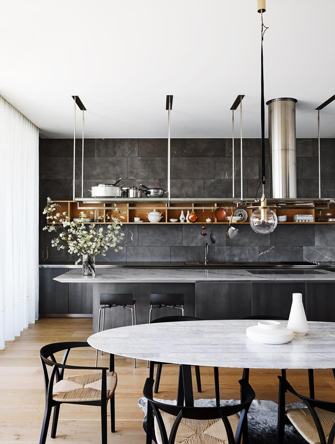 The Boffi kitchen is a nuanced use of stone, marble, timber with De Castelli heat-treated steel for a bronze patina effect on the cabinetry. Karakter Copenhagen vases from Cult on table. Flowers throughout by Hermetica.
