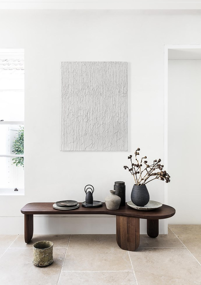 On the 'Kim' nesting table/bench by Nichetto from Spence & Lyda sit a bronze canister from Pure Interiors and a small 'Symbol' vase by Nicolette Johnson. Paul Wearing vessel (on floor) from Spence & Lyda. Shane Dunn artwork from Graphis Art + Framing.