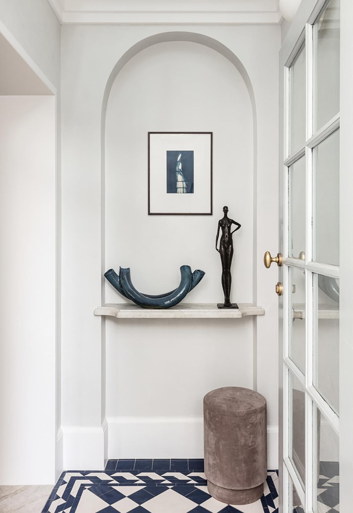 In the entry is a ceramic sculpture by Susie Solomon from Graphis Art + Framing and 'Sasha' by Corbin Bronze sculpture from Studio Cavit. Artwork by Laura Ellenberger. 'Tabou' pouf by Michael Verheyden from Ondene.