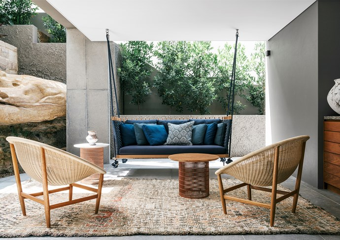 An intimate setting off the lower-ground floor, sheltered by the sandstone cliff. Paola Lenti 'Wabi' swing seat, Dedece. Kettal chairs and tables. Walter G cushions, Ascraft. Vase, Water Tiger. Rug, Cadrys.