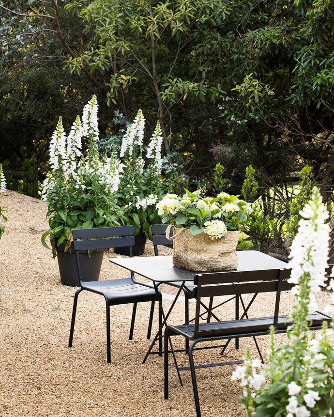 A sunny area outside the guest cottage with crunchy-gravel charm. Table and chairs, Cafe Culture+Insitu. Pots and foxglove plants from Julian Ronchi Garden Design & Nursery.