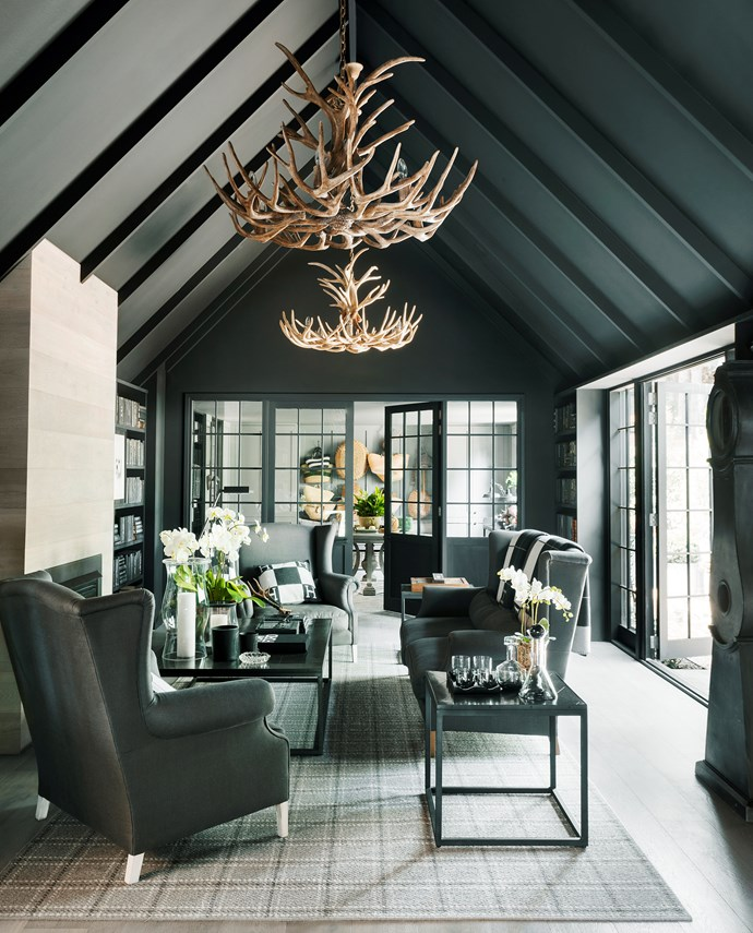 Matt-black paint on most of the walls and ceiling keeps this room  cosy. The fireplace is clad in the same oak as the floor. Antler chandeliers and grandfather clock, Restoration Hardware (US). Sofas covered in linen fabric from Westbury Textiles. Rug, Carpet World.