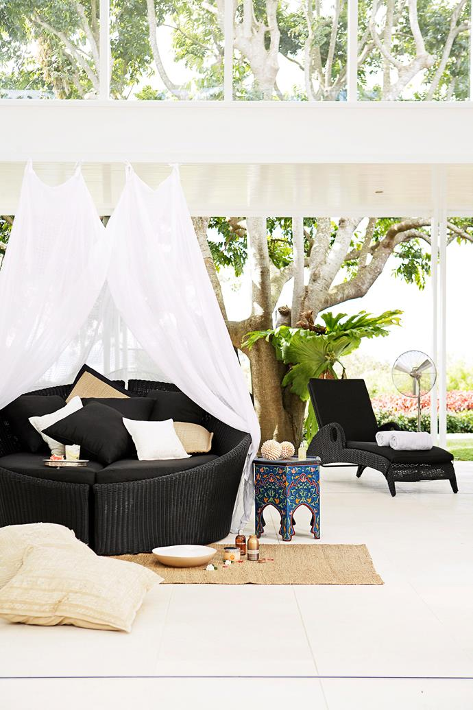 "If a built-in daybed isn't an option for your place, there are plenty of modular daybeds available from [outdoor furniture](https://www.homestolove.com.au/15-outdoor-furniture-picks-2179|target=""_blank"") retailers. This chic black design can be separated into two lounges or pushed together to create one cosy circular couch. A mosquito net strung up around it creates a private oasis. *Photo:* Prue Ruscoe"