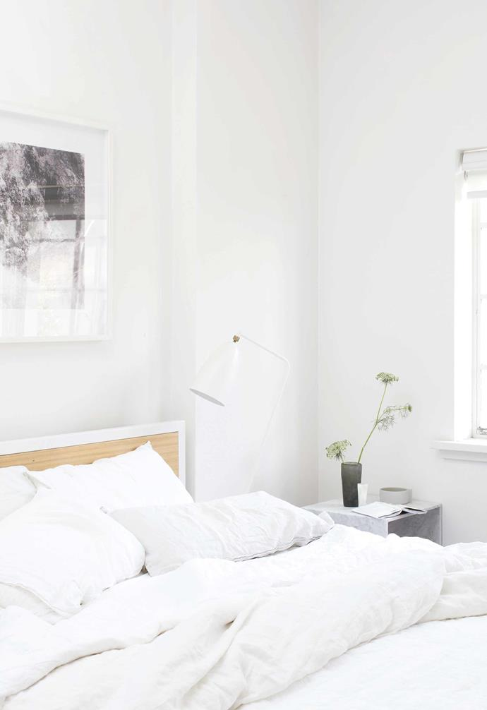 """**Master bedroom** The all-white scheme continues, broken up with the Tasmanian oak veneer headboard of an 'Oliver' bed from Hunting For George and a print from photographer Paul Blackmore's Waters series. Gubi 'grasshopper' floor lamp, [Cult](https://cultdesign.com.au/ Target=""""_Blank"""" Rel=""""nofollow""""). Side table, [Urban Couture](https://urbancouture.com.au/ target=""""_blank"""" rel=""""nofollow""""). Cases, [Dinosaur Designs](https://www.dinosaurdesigns.com.au/ target=""""_Blank"""" rel=""""nofollow"""")."""