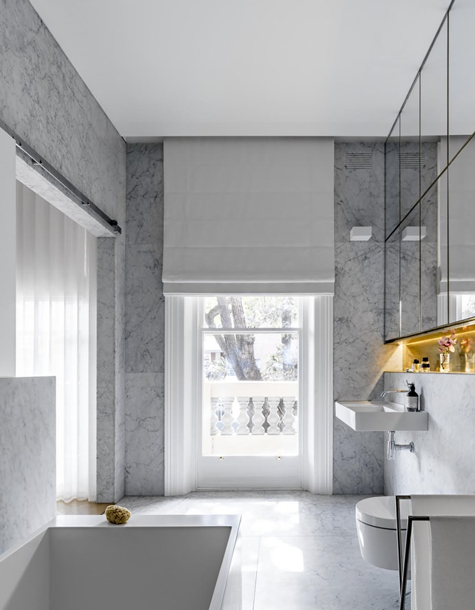 In the main ensuite, Laufen 'Kartell' bath and wall basin from Reece. Honed Carrara marble walls and floor from Nefiko Marble. Zucchetti 'Isy' basin mixer from Candana. 'Minimal' towel rack by Boffi. On the first-floor landing leading into the main bedroom, Buzzi & Buzzi 'Minimal' LED wall light from Analu.