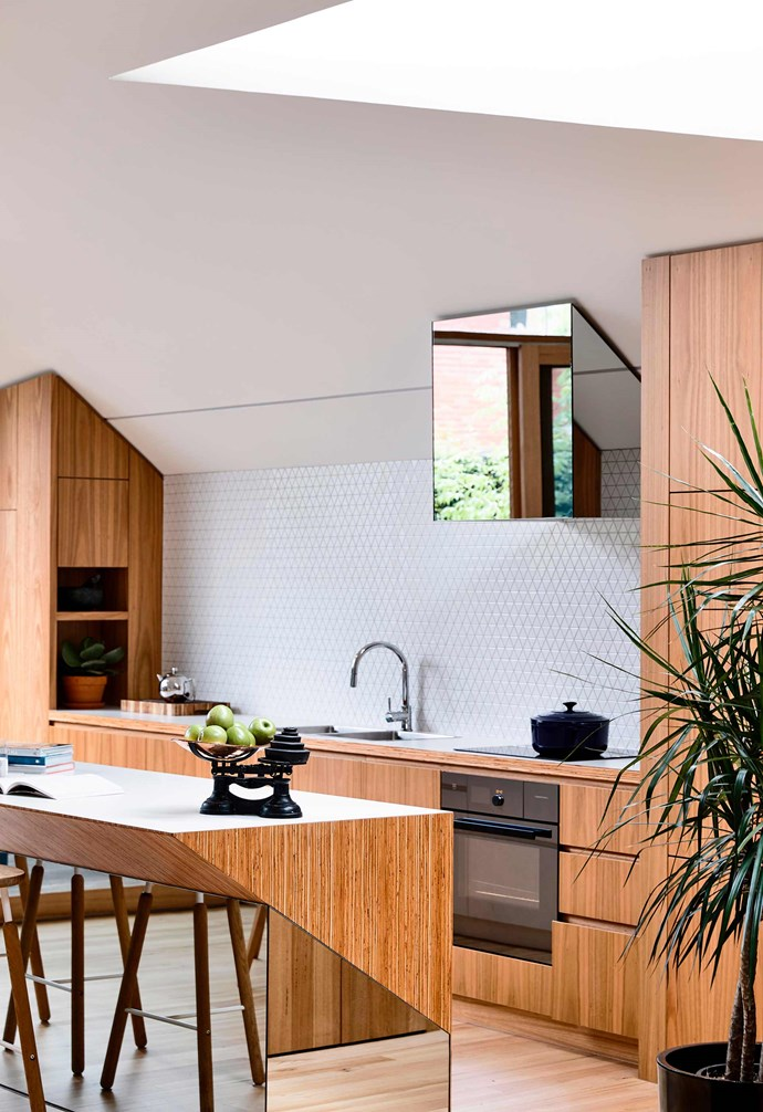 **Mirror magic** This kitchen island pairs mirrors with a timber surface with the mirror amplifying the natural light from the home's skylight, as well as making the home appear larger. *Photography: Derek Swalwell / bauersyndication.com.au*
