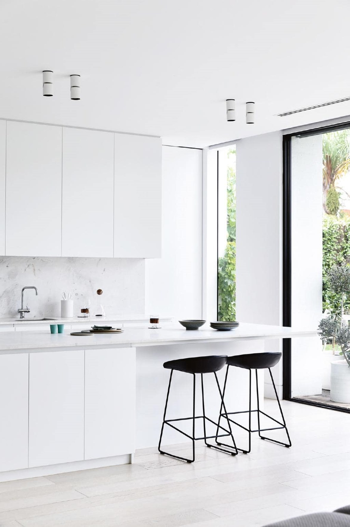 "Do away with tricky decisions surrounding colour palettes and instead opt for a simple all-white aesthetic. White kitchens are crowd pleasers, looking clean and fresh. In this [minimalist style home](https://www.homestolove.com.au/how-to-add-bright-colour-to-a-minimalist-style-home-18410|target=""_blank""), a kitchen island with marble benchtop adds texture while floor-to-ceiling windows connect the room to the great outdoors."