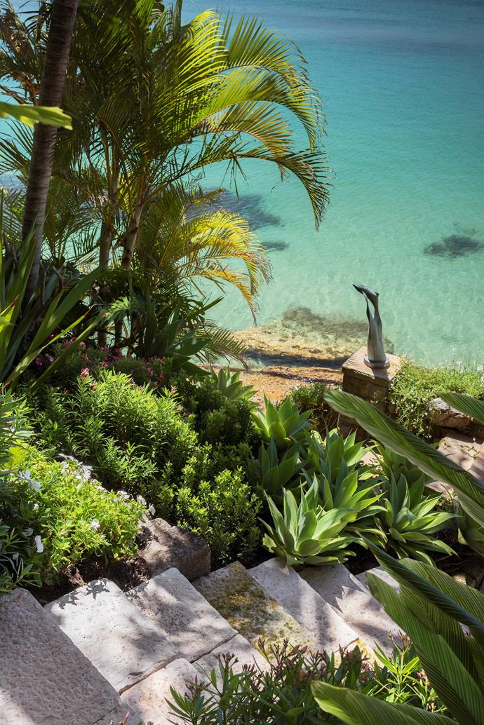 Stone steps lead to the waterside deck of this extravagant Sydney garden designed by Matthew Cantwell of Secret Gardens. Bronze sculpture with golden cane palms, agaves, dwarf oleander and *Raphiolepis* 'Snow Maiden.' *Photograph*: Nicholas Watt. From *Belle* February/March 2019.
