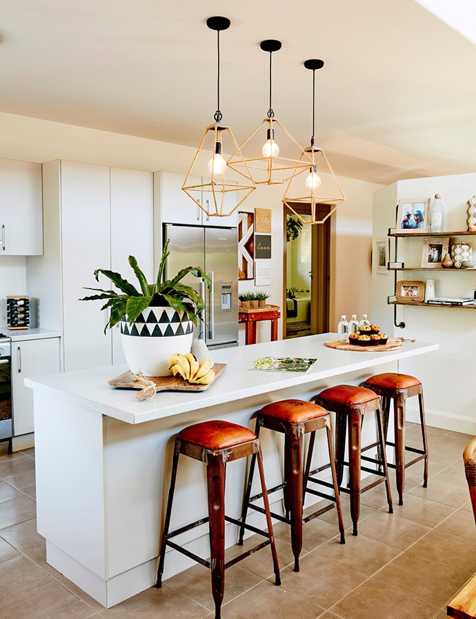 Subtle hints of colour are incorporated into this all-white kitchen with vintage bar stools and pendant lights. *Will Horner / bauersyndication.com.au*