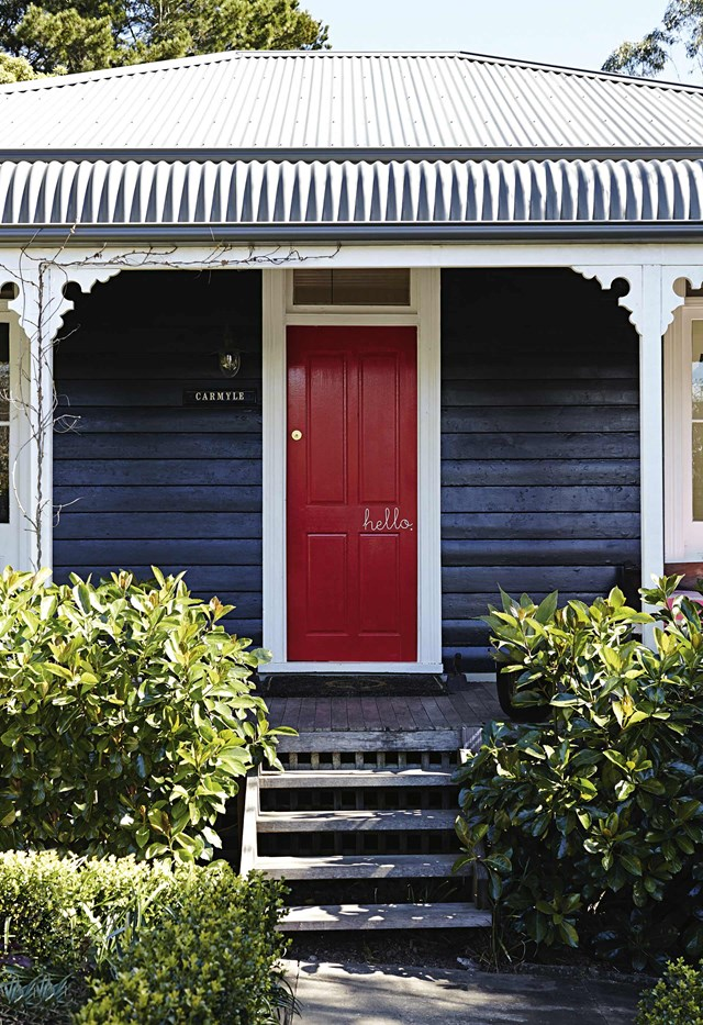 A bold front door doesn't have to be painted in an eye-popping hue. Here, a darker colour scheme of Taubmans' Black Fox and a rich red front door creates a dramatic yet sophisticated exterior perfectly suited to this Blue Mountains cottage. *Photo:* Alicia Taylor / *Inside Out*