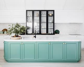 White kitchen with green island bench by Three Birds Renovations