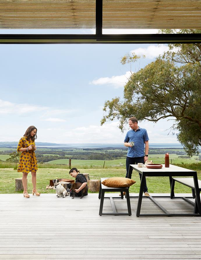 Owners Simone and David and daughter Mariella with their pugs, Molly (left) and Fu Manchu. In the distance is Corner Inlet, near Wilsons Promontory. Steel-framed eaves and awnings shield the home's interior from harsh summer sun. The deck and awning are silvertop ash. Freedom dining table and benches, bought through Gumtree. 'Junto' terracotta carafe by Simon Legald for Normann Copenhagen and 'Infinity' bowl in Ochre, both Lightly.