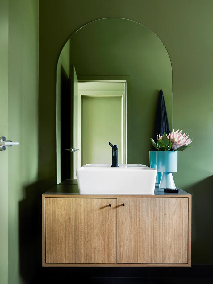 The vanity is a custom design by Archiblox. The front is finished in Laminex Sublime Teak, and the top and sides in Fossil. American Standard 'Heron' basin and Mizu 'Drift' mixer, both from Reece.