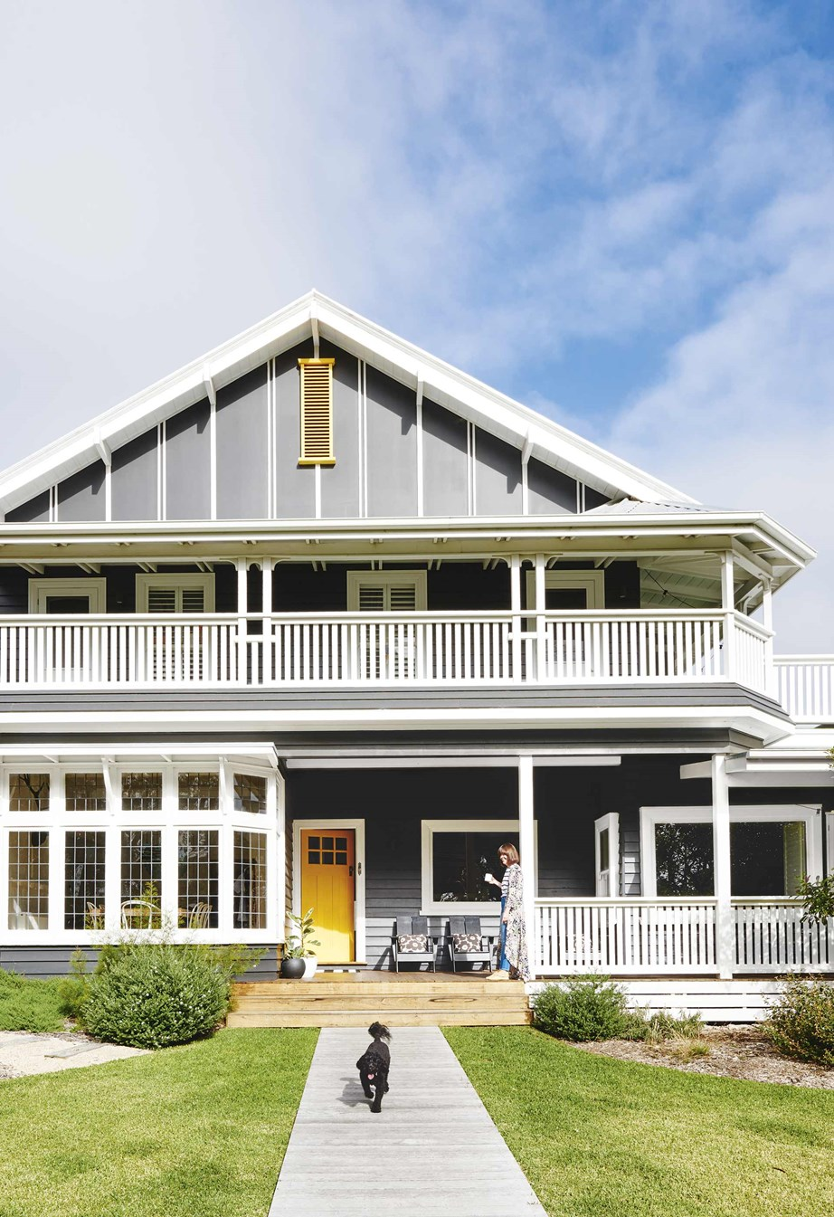 "Originally a faded green, the owner of this grand [1920s two-storey Californian bungalow](https://www.homestolove.com.au/californian-bungalow-barwon-heads-17909|target=""_blank"")  decided to give the house a more modern look by painting the weatherboards in Dulux Colorbond 'Monument' and the front door in Dulux 'Banana Boat'."