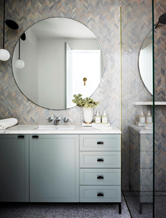 A custom mirror by Arent&Pyke sits in this serene powder room in a refurbished Sydney home conceived by Juliette Arent and Sarah-Jane Pyke. The pendant light is by Atelier Areti and the Aït Manos herringbone tiles are from Onsite Supply & Design. *Photograph*: Anson Smart. From *Belle* December/January 2018/19.