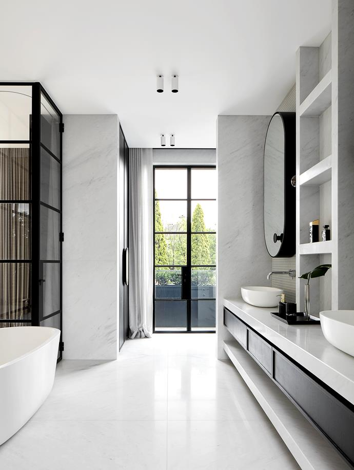 Bianco Carrara honed marble and black accents create an ultra-modern yet timeless effect in the bathroom of this Christopher Elliott-designed home. *Photograph*: Jack Lovel. From *Belle* November 2018.