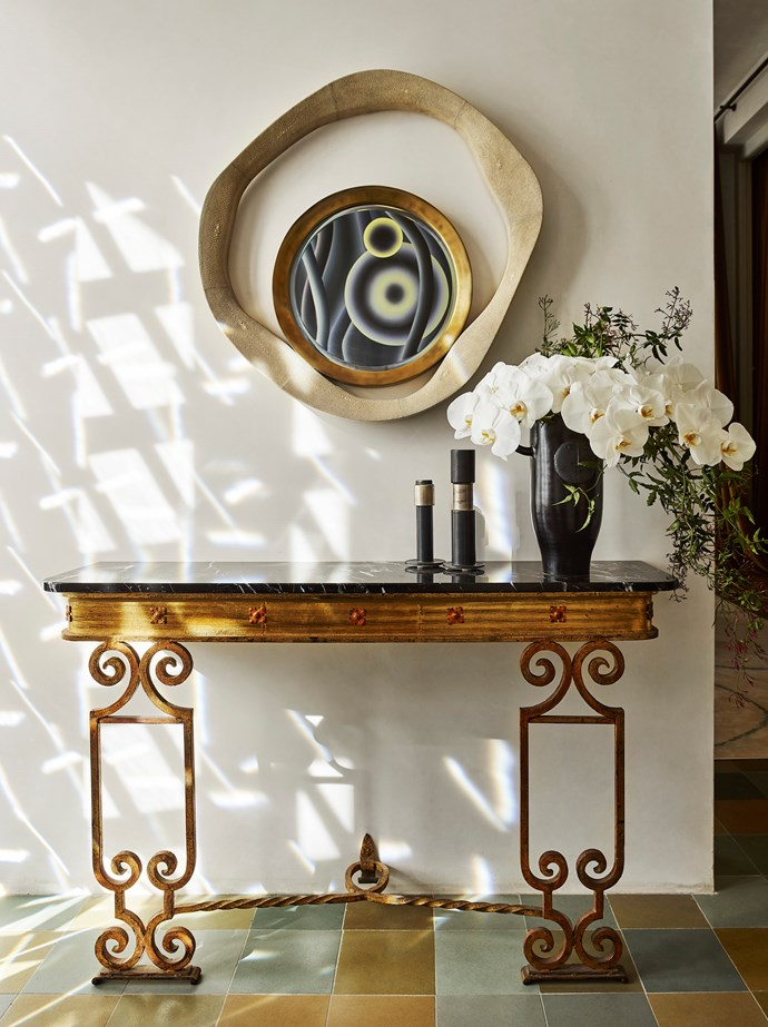 Marion Borgelt's Luna Tango No 3 is reflected in a handcrafted shagreen and bronze mirror from Editeur. Vintage Spanish gilded wrought-iron console with marble top from Editeur holds a black glazed vase by Les Dalo and porcelain candleholders by Porcelain Bear, all from Editeur.