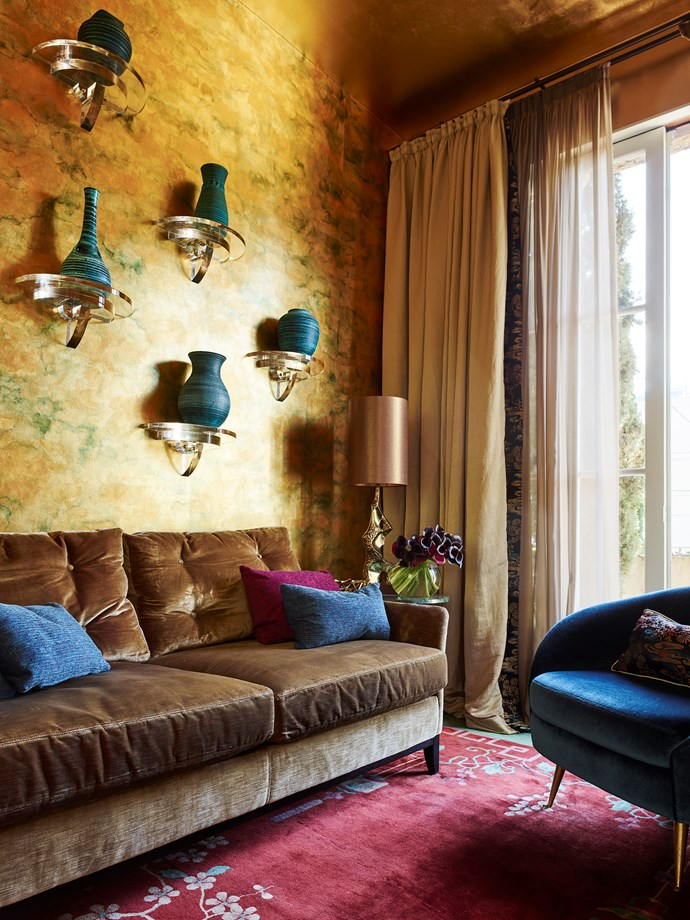 A gold tea wallpaper has been custom antiqued by de Gournay. A Christian Lyon-designed 'Salon' sofa is upholstered in Jim Thompson antique gold silk velvet. 'Saucer' armchair by Christian Lyon upholstered in Dominique Kieffer velvet. Collection of 1960s French Poterie d'Accolay on the wall. Vintage Shanghai art deco rug from Editeur.