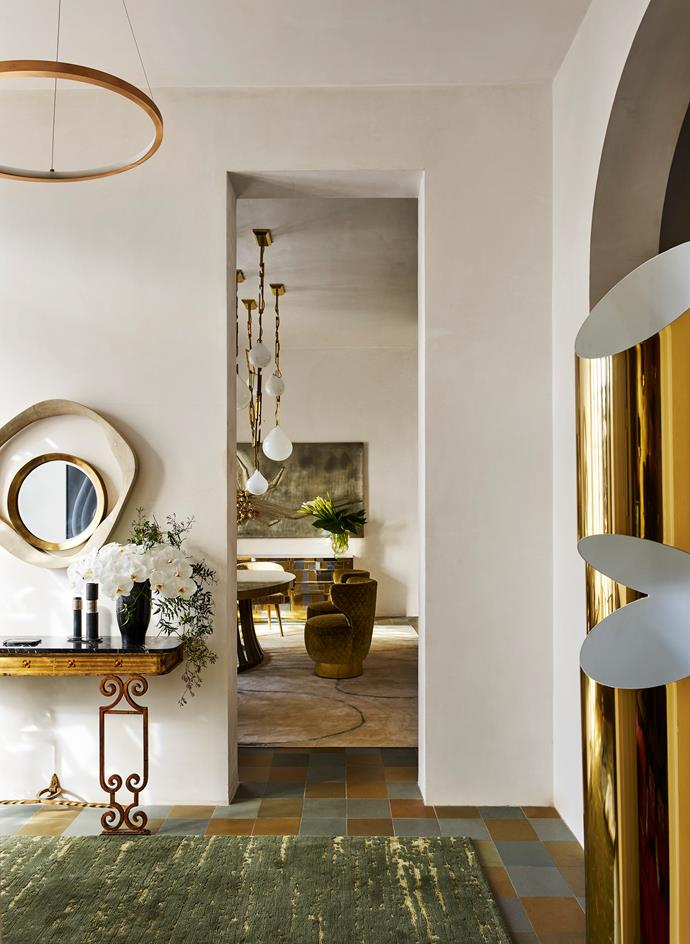 A vintage Spanish gilded wrought-iron console and handcrafted shagreen and bronze mirror from Editeur in the entrance. Porcelain Bear table in marble and porcelain with Tom Dixon 'Slab' chairs.