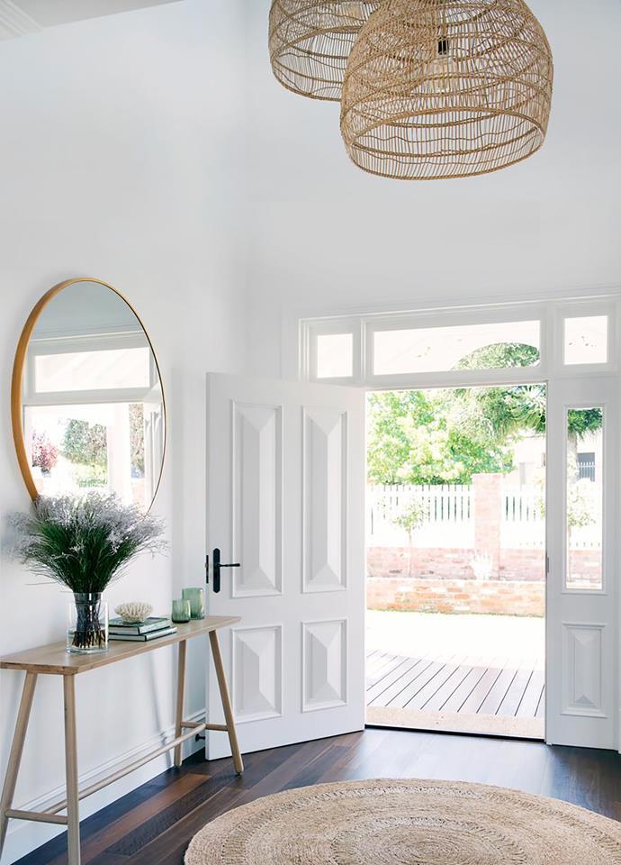 The foyer's high ceiling creates a sense of grandeur. HK Living pendant light, 'Bella' mirror, GlobeWest 'Linea' console and Armadillo & Co rug, all Cranmore Home.