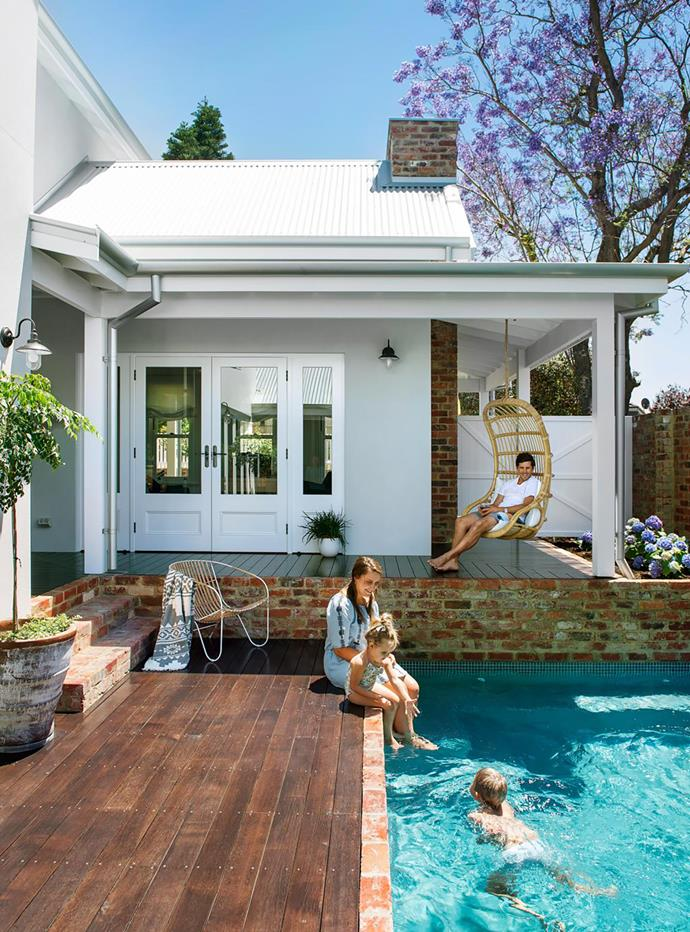 """Centrally locating the pool gave us more space for the backyard and creates lovely views from every room,"" says owner-builder Stafford Draper, pictured with his wife Jodie and children Tess and Jake. Doors and windows, Cedar West. Wall lights, Subiaco Restoration. 'Veranda' chair, Uniqwa Furniture. Fully compliant pool by Infiniti Designer Pools, using Ezarri 'Niebla' tiles. Local hero: 1970s Swing Chair, $499, Byron Bay Hanging Chairs."