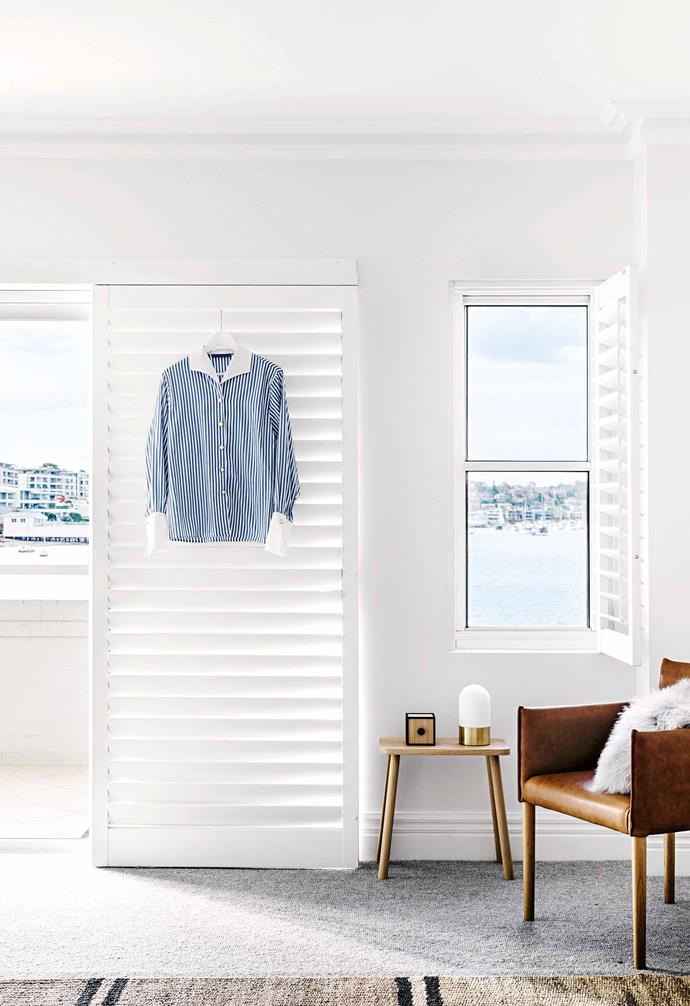 "**Into the blue** The master bedroom has sliding louvres that lead out onto a private verandah, overlooking the Parramatta River. ""There's a tranquil composure in the home that makes Mum feel like she's on holiday 24/7,"" says the owner's son. <br><br>**Tip**: Try louvres for both [windows and doors](https://www.homestolove.com.au/how-to-choose-doors-and-windows-18928