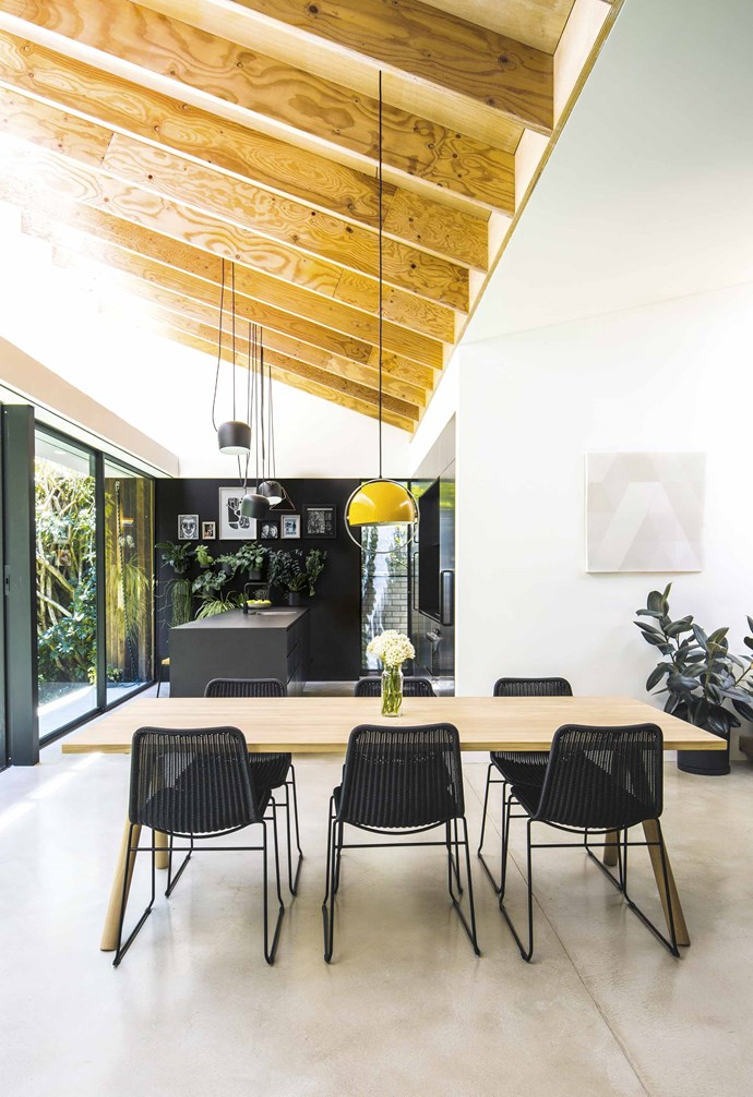 "**Dining area** [Exposed ceiling rafters](https://www.homestolove.com.au/shannon-vos-different-ceiling-types-and-why-they-work-15321|target=""_blank"") complement a Muuto 'Split' oak table from Living Edge, with Mark Tuckey 'Wicker' chairs continuing the kitchen palette. The artwork is a fibreglass cladding sample for a client's project. Brylle & Jacobsen 'Hanging Moon' pendant light, [1st Dibs](https://www.1stdibs.com/