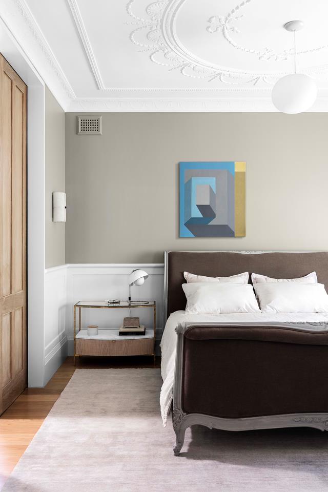 The original section of this home revamped by architect Telly Theodore features a muted and timeless colour palette, while heritage details including the ceiling roses and wainscoting have been preserved. Bed from MCM House. Custom bedside console by Telly Theodore. Verner Panton table light from Great Dane. Flos 'Glo-Ball' pendant by Jasper Morrison from Living Edge. Rug by Armadillo & Co. Artwork by Adrian Hobbs. *Photograph*: Tom Ferguson. From *Belle* August/September 2018.