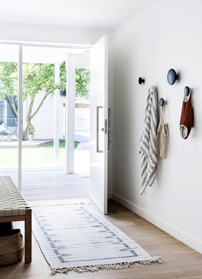 "A set of Muuto ""Dots"" wall hooks create the perfect grab-and-go storage at the front door. The bench is from Space to Create, with Olli Ella baskets underneath, and the rug is from Marr-Kett in Byron Bay."