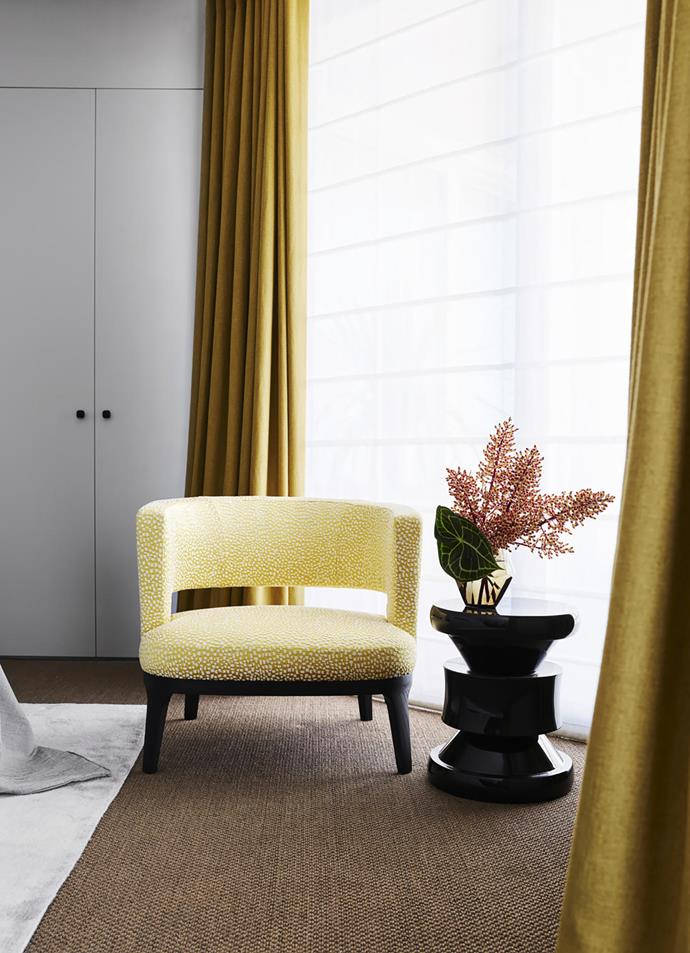 A chair in the guest bedroom from Fanuli with curtains by Simple Studio.