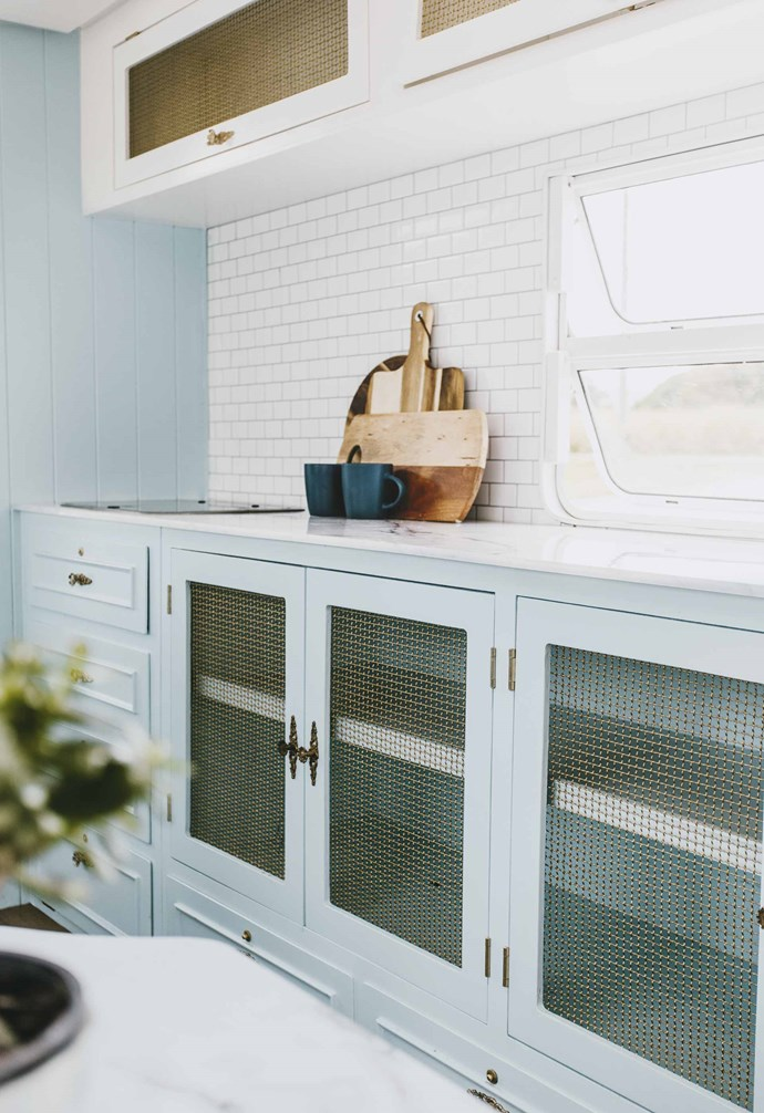 "**Cabinets** Old glass [cupboard fronts](https://www.homestolove.com.au/kitchen-cabinets-your-guide-to-choosing-right-5610|target=""_blank"") were removed and given a style update with brass wire netting."